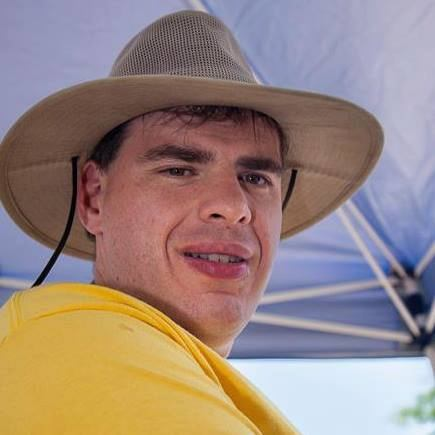 a photo of Matt Smith in a yellow shirt and a hat, under an umbrella on a warm day